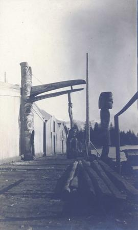 Four totem poles in front of various buildings