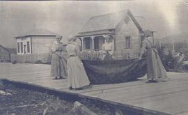 Four women cleaning a rug on a wooden walkway