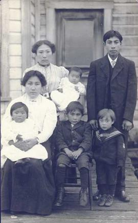 First Nations family - two older girls, both holding children, two younger boys and one older boy