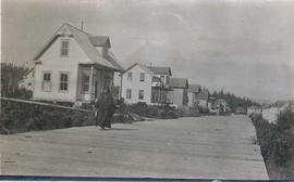 Elderly First Nations woman walking on wooden walkway in front of some houses