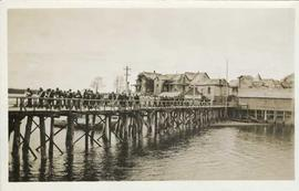 Large group of people walking along a wooden walkway on pilings