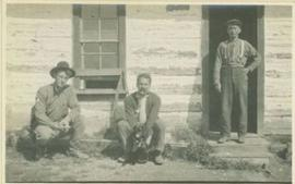 Two men sitting beside a house and another standing at the front door