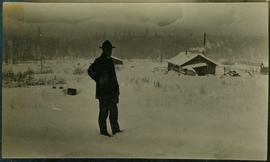 A man standing in front of a cabin