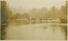 Men leading their horses across a river