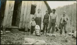 A First Nations family outside a log building