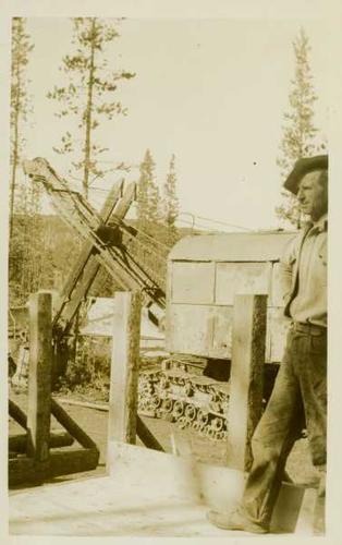 Unidentified man standing on a wooden road beside a steamshovel