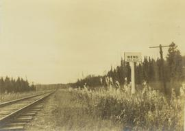 """Bend one mile"" sign posted next to a railway track"