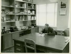 Prince Rupert Daily News - Man writing at a desk in the Reporter's Room