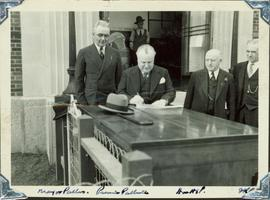 Harry Perry standing next to BC Premier Pattullo while he signs a document