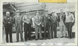 Harry Perry standing with a group of eight men