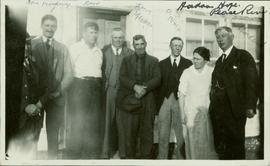 Group photo featuring eight people standing outside a home in Hudson Hope