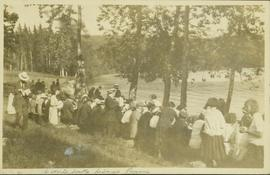 People sitting at a long row of picnic tables at a Liberal Party picnic