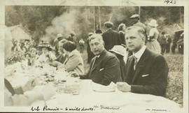 Hon. W. Sutherland and Alex Manson sit at a picnic table at a Liberal Party picnic
