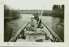 Three men seated in the stern of a boat sailing on Crooked River