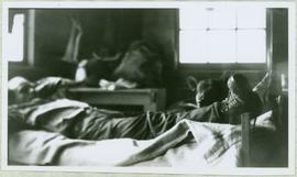 Man and Dog Reclining in Bunkhouse