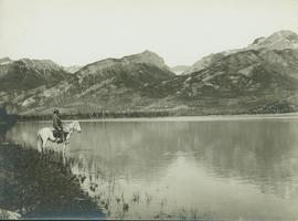 Unidentified man on horseback standing next to Brule Lake looking west