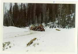 Arch-logging truck dragging a large load of logs uphill on a snowy road